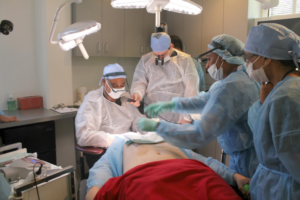 Los Angeles hair restoration surgeon, Dr. Umar performing live surgery to demonstrate the use of his Advanced FUE technology to his colleague physicians at an ISHRS regional workshop